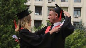 Donna bionda in vestito da graduazione che abbraccia migliore amico dopo la ricezione del diploma video d archivio