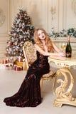 Donna bionda in vestito da sera con vetro dell'ubicazione del champagne o del vino bianco su una sedia nell'interno di lusso Albe Immagini Stock