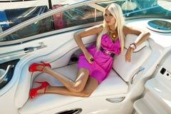 Donna bionda in vestito rosa sulla barca, vacanza estiva sulla barca a vela fotografie stock