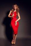 Donna bionda in vestito rosso che tiene vetro di champagne Fotografie Stock Libere da Diritti