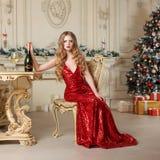 Donna bionda in vestito rosso con vetro dell'ubicazione del champagne o del vino bianco su una sedia nell'interno di lusso Albero Fotografia Stock
