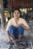 Donna birmana che indossa trucco tradizionale di tanaka con i suoi strumenti che fanno i coltelli del metallo fotografia stock