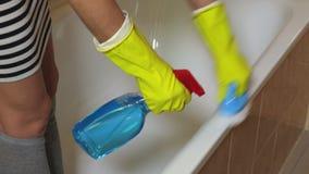 Donna in bordo pulito del bagno dei guanti gialli