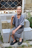 Donna bulgara anziana povera con la canna di camminata e consumata, vestito misero che si siede sulle scale sulla via di Varna Fotografia Stock Libera da Diritti
