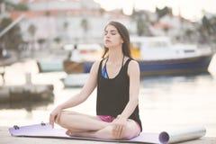 Donna in buona salute adatta che allunga sulla stuoia di yoga sulla spiaggia della spiaggia, facente gli scricchiolii di esercizi Immagine Stock Libera da Diritti