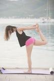 Donna in buona salute adatta che allunga sulla stuoia di yoga sulla spiaggia della spiaggia, facente gli scricchiolii di esercizi Immagini Stock