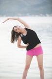 Donna in buona salute adatta che allunga sulla stuoia di yoga sulla spiaggia della spiaggia, facente gli scricchiolii di esercizi Immagine Stock