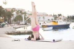 Donna in buona salute adatta che allunga sulla stuoia di yoga sulla spiaggia della spiaggia, facente gli scricchiolii di esercizi Fotografia Stock Libera da Diritti