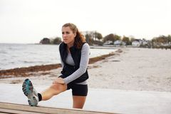 Donna in buona salute che allunga dopo l'allenamento sulla spiaggia Fotografia Stock Libera da Diritti