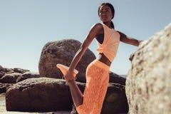 Donna in buona salute che allunga le gambe prima dell'correre alla spiaggia Immagine Stock Libera da Diritti