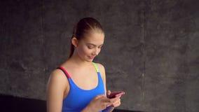 Donna in buona salute che controlla le statistiche del corpo sullo Smart Phone dopo l'allenamento alla palestra facendo uso della video d archivio