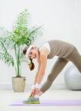Donna in buona salute che fa allungamento delle esercitazioni Fotografia Stock