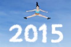 Donna in buona salute che salta sopra i numeri 2015 Immagini Stock