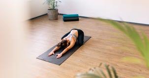 Donna in buona salute che si esercita sulla stuoia di yoga all'interno Fotografie Stock