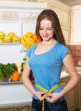 Donna in buona salute che sta vicino al frigorifero aperto in pieno delle verdure fotografia stock libera da diritti