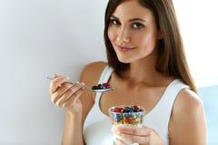 Donna in buona salute della prima colazione con vetro di yogurt, delle bacche e dell'avena Fotografie Stock Libere da Diritti