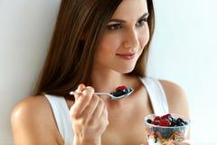 Donna in buona salute della prima colazione con vetro di yogurt, delle bacche e dell'avena Immagine Stock