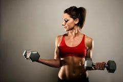 Donna in buona salute di forma fisica che flette i suoi muscoli Fotografia Stock