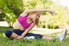Donna in buona salute e bella che fa allungando esercizio in parco Immagine Stock