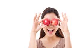 Donna in buona salute ed allegra che la copre occhi di due mele rosse immagine stock