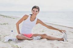 Donna in buona salute felice che sorride mentre facendo allungamento della gamba Fotografia Stock