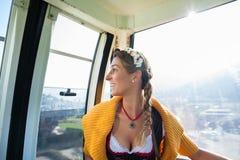 Donna in cabina di funivia che va sulle montagne Fotografia Stock