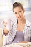 Donna in caffè d'offerta del pigiama Immagini Stock