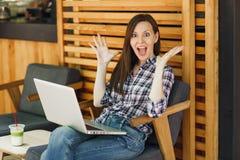 Donna in caffè di legno della caffetteria di estate della via di aria aperta che si siede in abbigliamento casual, lavorante al c fotografie stock libere da diritti