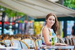 Donna in caffè parigino con il cocktail un giorno di estate Immagini Stock Libere da Diritti