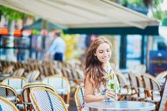 Donna in caffè parigino con il cocktail un giorno di estate Fotografie Stock Libere da Diritti