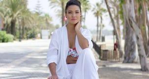 Donna calma in abito bianco che si siede all'aperto archivi video