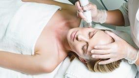 Donna calma che gode del trattamento di cura di pelle al centro di benessere video d archivio
