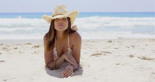 Donna calma che risiede nella sabbia sulla spiaggia video d archivio