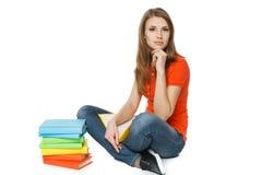 Donna calma che si siede sul pavimento con la pila di libri Fotografia Stock Libera da Diritti