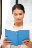 Donna calma e seria con il libro Immagini Stock