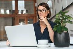 Donna calma in occhiali che funzionano con il computer portatile Immagini Stock Libere da Diritti