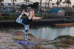 Donna in calzamaglia del modello che funzionano flessibilità ed equilibrio all'alba Immagini Stock