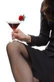 Donna in calze a rete nere che tengono cocktail Fotografie Stock Libere da Diritti