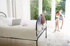 Donna in camera da letto che mette sulle scarpe Fotografia Stock