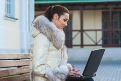 Donna in camice che si siedono sul banco Fotografia Stock Libera da Diritti