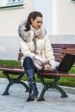Donna in camice che si siedono sul banco Fotografie Stock Libere da Diritti