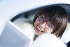 Donna in camice con la risata del ipad Fotografia Stock