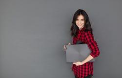 Donna in camicia casuale che sorride e che tiene un computer portatile Immagine Stock Libera da Diritti