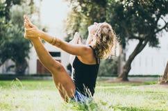 Donna in canottiera sportiva nera dei jeans che fa posa di yoga di konasana di upavistha in parco fotografia stock