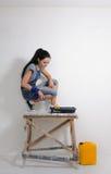 Donna capace che dipinge la parete della sua casa fotografia stock