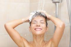 Donna in capelli di lavaggio dell'acquazzone Fotografia Stock