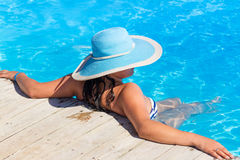Donna in cappello blu alla piscina Immagine Stock