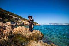 Donna in cappello che sta su una roccia e che guarda all'orizzonte più Fotografia Stock