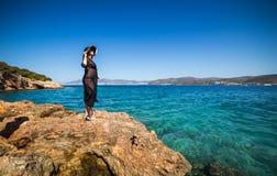 Donna in cappello che sta su una roccia e che guarda all'orizzonte più Immagini Stock Libere da Diritti