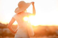 Donna in cappello con i grandi campi, al tramonto Fotografia Stock Libera da Diritti